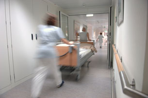 Nurses pushing hospital bed, gurney